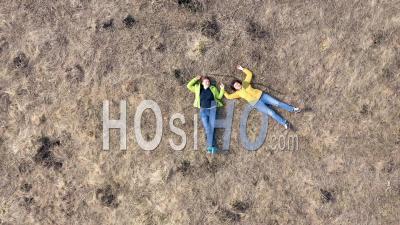 Drone View Of Girls Laying In A Meadow - Drone Point Of View