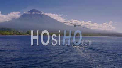 Fishing Boat And Mount Agung With Wispy Activity Between Eruptions - Video Drone Footage