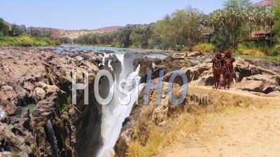 Vue Aérienne De Deux Femmes De La Tribu Himba Devant Des Cascades D'epupa à La Frontière Entre L'angola Et La Namibie, En Afriqu - Vidéo Drone