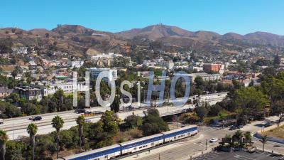 Aerial Video Drone Footage Of The Pacific Surfline Amtrak Train Passing Through The Southern California Beach Town Of Ventura, California With Freeway Foreground And Mountains Background