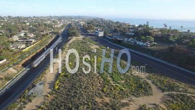 Aerial View Over An Amtrak Train Traveling Beside The Pacific Ocean Near San Diego - Video Drone Footage