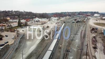 Aerial View Of The Southwest Chief Amtrak Train Traveling Through A Railroad Yard Near Burlington, Iowa - Video Drone Footage