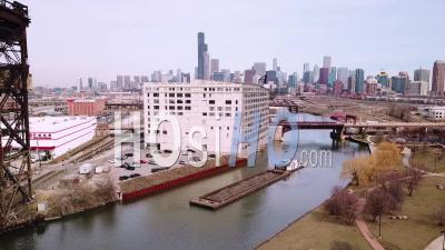 Aerial View Over A Barge Traveling Along The Chicago River With City Of Chicago Skyline Background - Drone Point Of View