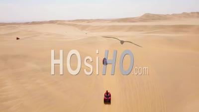 Aerial View Over Atv Vehicles Speeding Across The Desert Sand Dunes In Namibia, Africa - Video Drone Footage