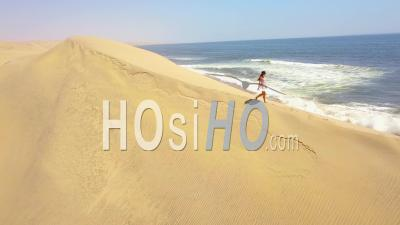 Aerial View Over A Model Released Woman Walking On Magnificent Sand Dunes On The Skeleton Coast, Namibia - Video Drone Footage