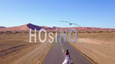 Aerial View Over A Woman Walking With A Suitcase Or Rolling Bag On A Lonely Road In The Namib Desert In Namibia, Africa - Drone Point Of View