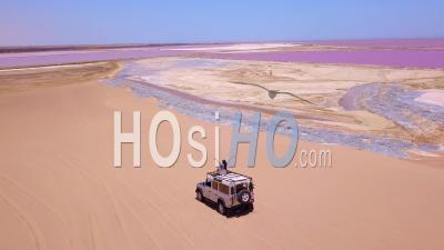 Aerial View Over A Woman Sitting On Top Of A 4wd Safari Jeep On A Colorful Pink Salt Flat Region In Namibia, Africa - Video Drone Footage