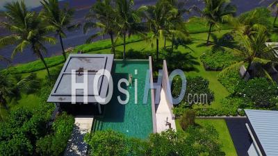 Vue Aérienne Sur Une Femme Nageant Dans Une Piscine à Débordement Au Complexe Hôtelier De Luxe D'un Complexe Résidentiel élégant Le Long De La Côte De Bali, Indonésie -Vidéo Drone