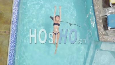 Aerial View Of A Sexy Woman Relaxing At A Pool Of A Condo Or Luxury Home On The Caribbean Island Of St. Lucia - Video Drone Footage