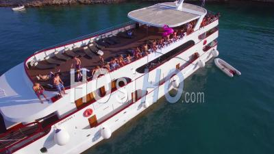 Swimmers And Partiers Jump Off A Large Yacht Or Boat In The Adriatic Sea Near Croatia During A Yacht Party - Video Drone Footage