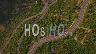 Aerial View Of Cars Navigating On A Very Narrow Winding Mountain Road With Many Switchbacks And Hairpin Turns - Video Drone Footage