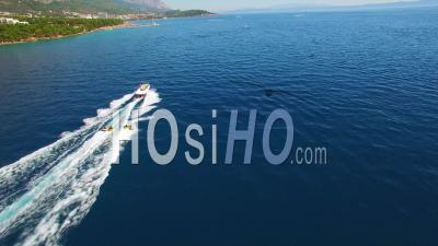 Aerial View Of Adventure Boat Towing Four Innertubes For A Tubing Adventure Off The Coast Of Croatia - Video Drone Footage