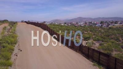 Aerial View Along The U.S Mexican Border Wall Fence Reveals The Town Of Tecate Mexico - Video Drone Footage