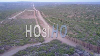 Le Drapeau Américain Flotte Au-Dessus De La Frontière Entre Les États-Unis Et Le Mexique Dans Le Désert De Californie Alors Qu'une Patrouille Frontalière Passe Sous - Vidéo Drone