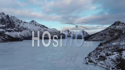 Frozen Lake With Ice On It With Mountains In The Background - Video Drone Footage