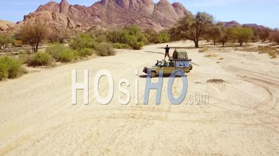 Aerial View Over A Man Standing On A 4wd Safari Camper Van Taking Photos Of Rock Formations At Spitzkoppe, Namibia, Africa - Video Drone Footage