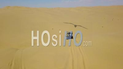 Aerial View Over 4wd Safari Land Rover 4x4 Driving Over Desert Sand Dunes In The Namib Desert, Namibia, Africa - Video Drone Footage