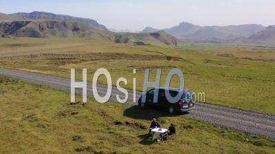 Vue Aérienne Sur Deux Hommes Bénéficiant D'un Pique-Nique à Côté D'un Fourgon De Camping Noir Dans Les Montagnes D'islande - Vidéo Drone