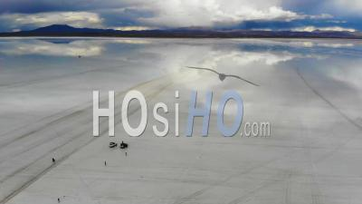 Aerial View Of People Gathering On The Uyuni Salt Flats Lake With Perfect Reflections In Bolivia - Video Drone Footage