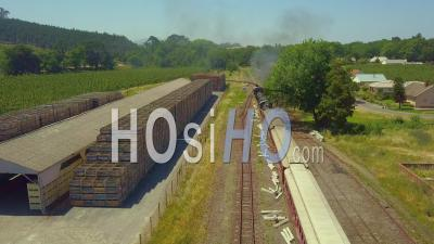 Steam Train Pushing Carriages Into Rural Station - Video Drone Footage