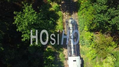 Steam Train Coming To Stop In Wooded Area - Video Drone Footage