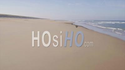 Retired Woman Having A Walk On A Desert Beach By The Atlantic Ocean - Drone Point Of View
