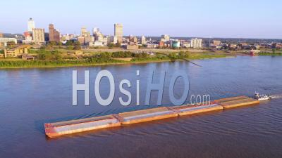 A Barge On The Mississippi River With Downtown Business District Of Memphis Tennessee In Background - Aerial Video By Drone