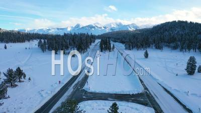 2020 - Aerial Video Of Cars Driving Slowly On Icy Snow Covered Mountain Road In The Eastern Sierra Nevada Mountains Near Mammoth California - Video Drone Footage
