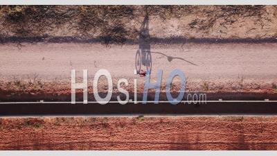 Moto Conduisant à Travers Une Route De Sable Rouge Déserte Jetant Une Ombre - Vidéo Drone