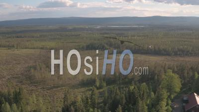Aerial View Of A Helicopter Getting Close To Houses In Forest, Tackasen, Sweden - Video Drone Footage