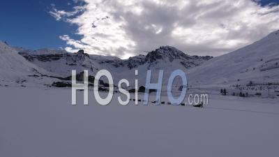 People On Sleds With Dogs Moving On A Frozen Lake, Tignes, France - Video Drone Footage