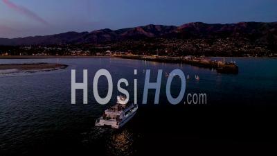 2020 - Night Dusk Or Twilight Aerial Over A Fishing Boat Entering Santa Barbara Harbor. - Video Drone Footage