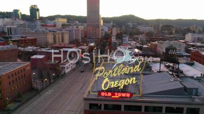 Aerial Around Portland Oregon Stag Deer Sign And Downtown Old Town Cityscape And Business District At Sunset Or Dusk. - Video Drone Footage