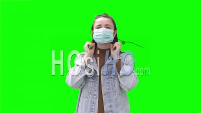 Young Woman Putting On Face Mask
