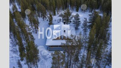 Aerial Drone Photo Of Wooden Cabin In The Remote Forest, With Snow Covered Woods And Trees Landscape In Lapland, Finland