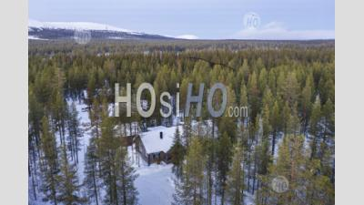 Aerial Drone Photo Of Wooden Cabin In The Remote Forest, With Snow Covered Trees Landscape And Mountains In Lapland, Finland