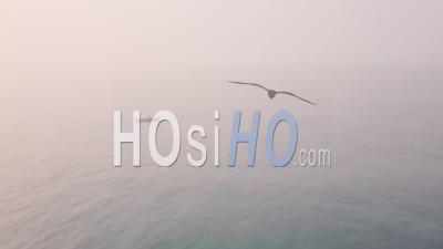 Fishing Boat At Sea At Sunrise, Net Fishing. Aerial Drone View