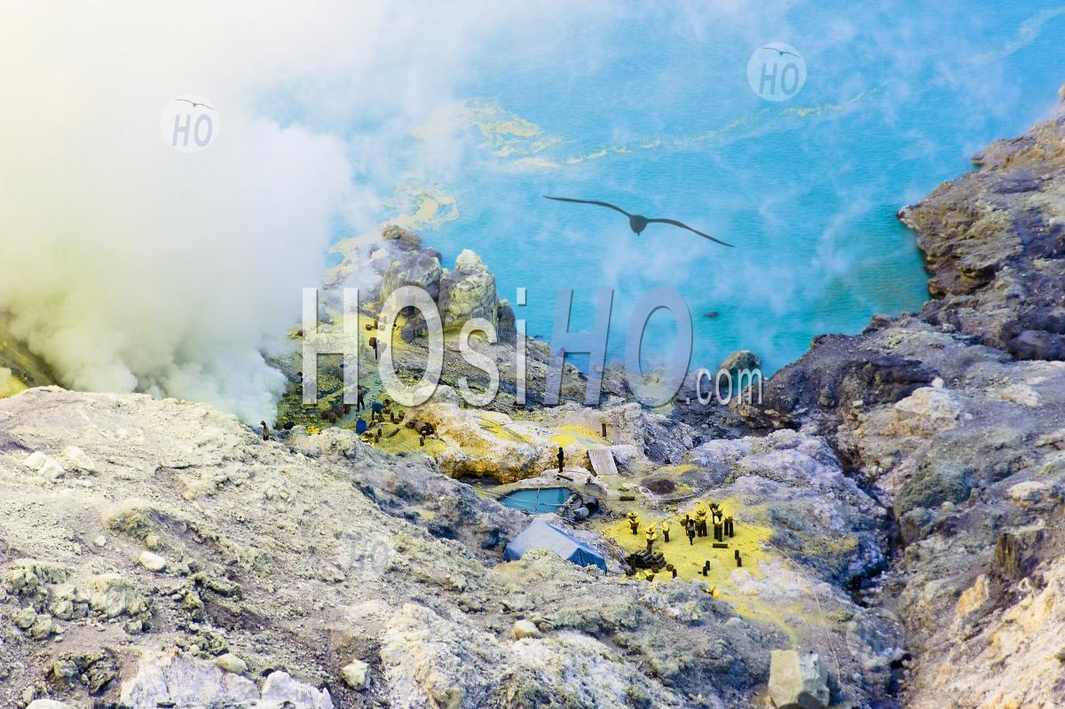 Birds Eye View Of Sulphur Miners Working By The Turquoise Acid Crater Lake At Kawah Ijen, Java, Indonesia