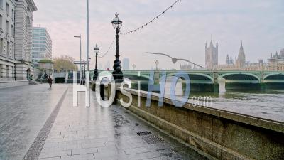 London In Coronavirus Covid-19 Lockdown With Person Walking In Deserted Empty Streets By River Thames With Houses Of Parliament Behind Westminster Bridge In England, Uk