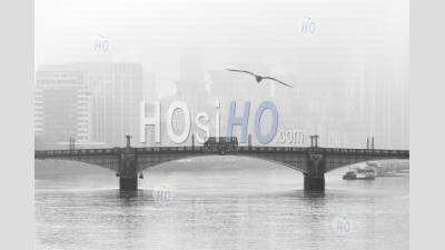 Black And White Central London City Skyline With Iconic London Bus Driving Over Lambeth Bridge With Misty Foggy Skyscraper Buildings Shot In Coronavirus Covid-19 Lockdown In England, Uk