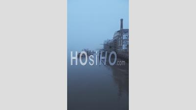 Vidéo Verticale De La Tamise Et Butlers Wharf Pier à Londres Dans Un épais Brouillard Et Brume, Sur Un Matin Bleu Frais Dans Le Brouillard Et Le Temps Moody Brumeux à Covid-19 Coronavirus Lockdown, England, Uk