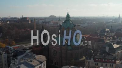 Scenic View Of A Cathedral In Winter Sunlight With Green Roof And Church Tower In Munich, Germany Neighborhood Right By The Isa River - Video Drone Footage