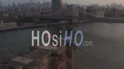 Close Up Of Brooklyn Bridge With American Flag And Beautiful Sunrise Morning Light Over East River In New York City 4k - Video Drone Footage