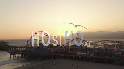 Vue Rapprochée De La Grande Roue De La Jetée De Santa Monica, Los Angeles Au Magnifique Coucher De Soleil Avec Les Touristes, Les Piétons Marchant S'amusant Au Parc à Thème Rollercoaster Avec Vue Sur L'océan Waves S'écraser 4k - Drone Vidéo