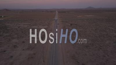 Vol Au-Dessus D'une Route Désertique Abandonnée Solitaire Avec Une Voiture Rouge Conduisant Au Loin 4k - Vidéo Aérienne Par Drone