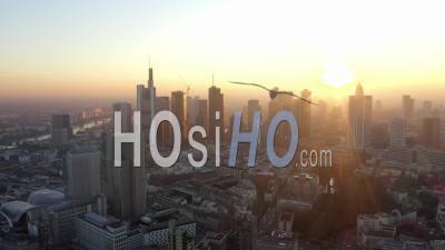 Vue Aérienne De Francfort-Sur-Le-Main, Allemagne Skyline Avec Sunflair Jaune Doré Entre Les Gratte-Ciel Dans Le Beau Coucher De Soleil Au Soleil En Hiver Brume 4k - Séquence De Drone Vidéo