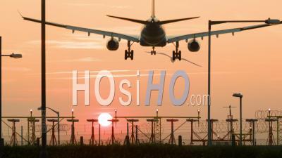 Avion De Passagers Atterrissant Au Coucher Du Soleil