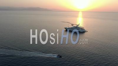 Fast Zodiac Boat In Front Of Luxury Yacht In The Sunrise On The Bay Of Antibes, French Riviera, Filmed By Drone, France