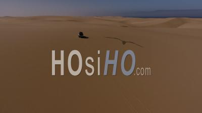 White Pick Up Driving Forward On Sand Dune In The Namib Desert, Atlantic Ocean On The Left, Followed By Drone